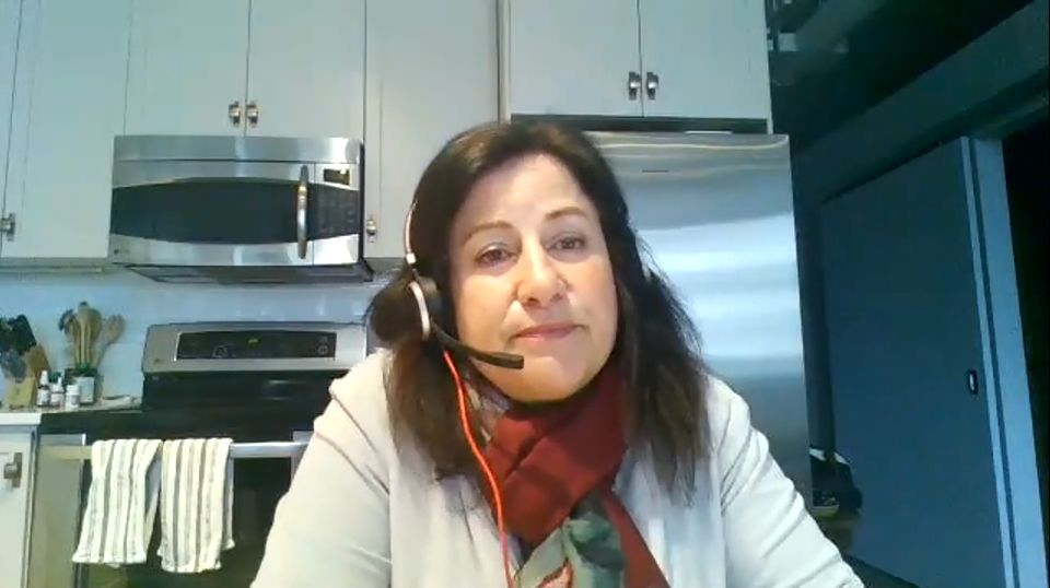 An image of Hamilton City Manager Janette Smith in her home kitchen wearing a computer headset during a video conference with the Hamilton Chamber of Commerce