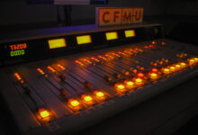A radio station control board showing the dials glowing in a dark room