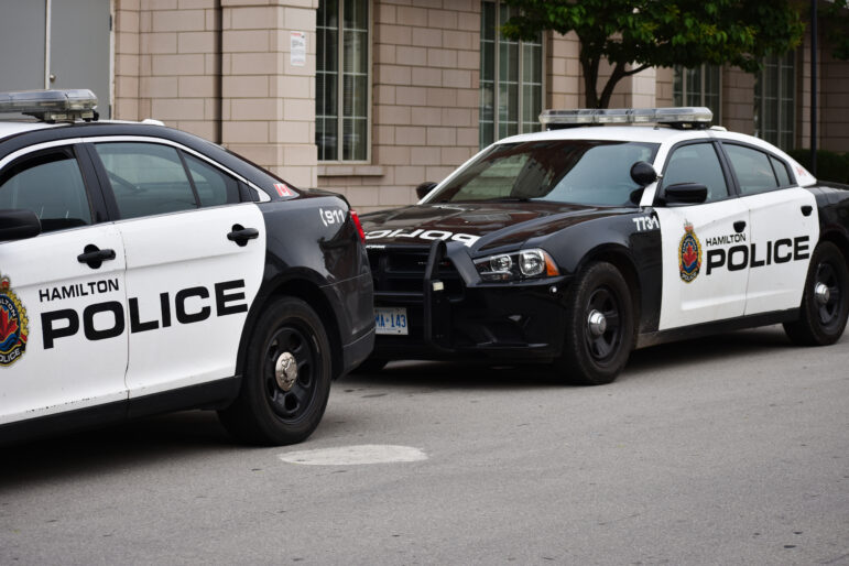 Two Hamilton Police Cruiser cars on a street.