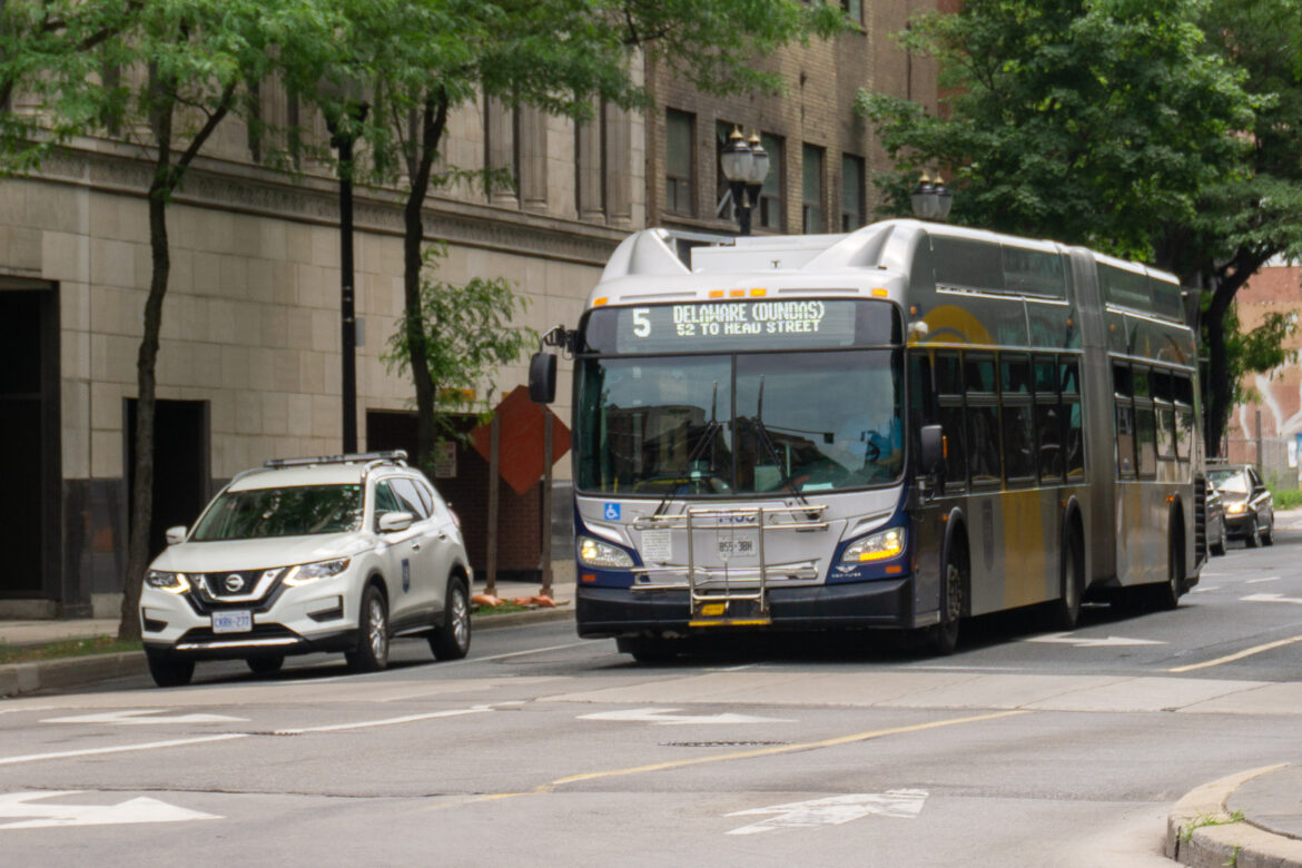 Photo shows a HSR supervisor car on the right, with a HSR 60-foot articulated bus to its left. Both are waiting at an intersection during a red light.