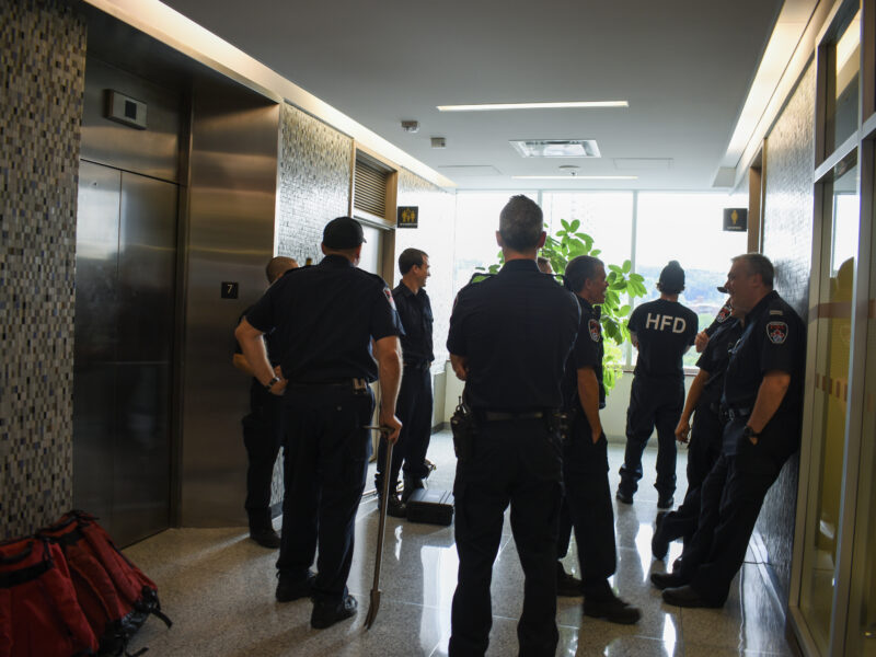 Hamilton firefighters standing in a lobby awaiting an elevator mechanic to rescue a person trapped inside a stalled elevator