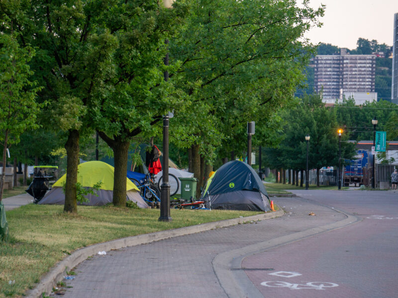 photos shows a group of tents alongside a roadway